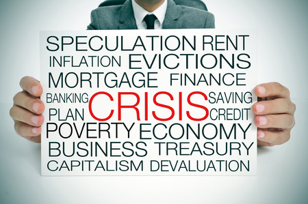 subprime mortgage crisis: a businessman holding a signboard with different terms related to the economic crisis concept