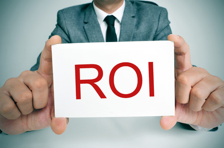 bank rate: businessman sitting in a desk showing a signboard with the text ROI, ROI, acronym for Rate of Interest or Return on Investment, written in it