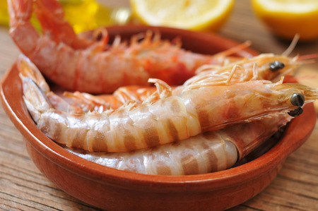deepsea: closeup of a earthenware bowl with some fresh raw shrimps on a rustic wooden table