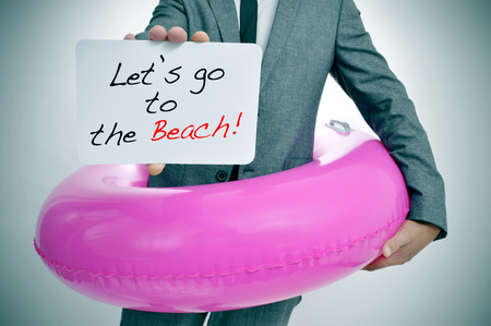 businessman with a pink swim ring showing a signboard with the text lets go to the beach written in it Banco de Imagens