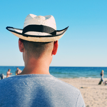 heat radiation: back view of a young man with a straw hat hanging out on the beach