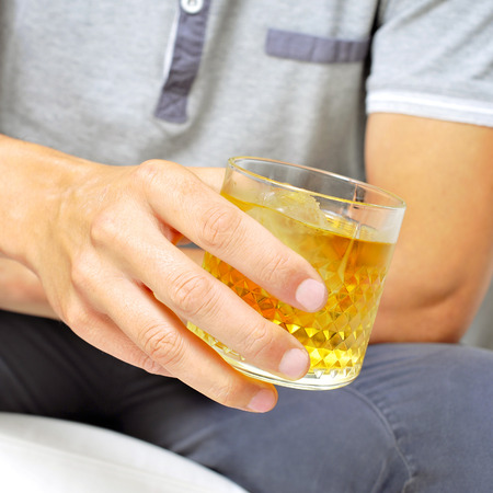 addictive drinking: young man hanging out with a glass of liquor Stock Photo