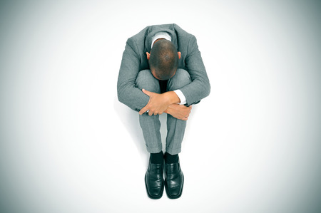 ruination: a businessman curled up in the floor with his head between his knees