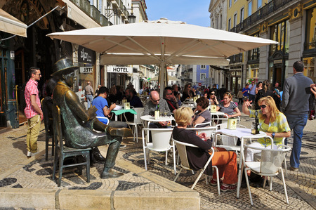 chiado: LISBON, PORTUGAL - MARCH 17: The crowded terrace of Cafe A Brasileira with the Statue of Fernando Pessoa on March 17, 2014 in Lisbon, Portugal. This statue and the cafe are visited for many tourists