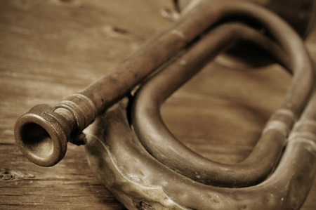 reveille: old bugle on a rustic wooden table, in sepia tone