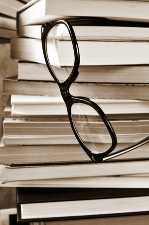 a pair of eyeglasses on a pile of books, in black and white photo