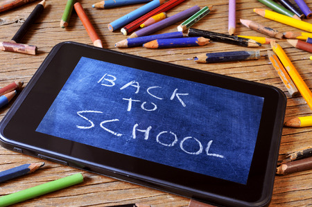 school aged: a tablet with a picture of a chalkboard with the sentence back to school written in it, on a rustic wooden desk with worn pencil crayons of different colors Stock Photo