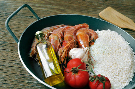 ingredients to prepare a spanish paella or arroz negro on a rustic wooden table Imagens