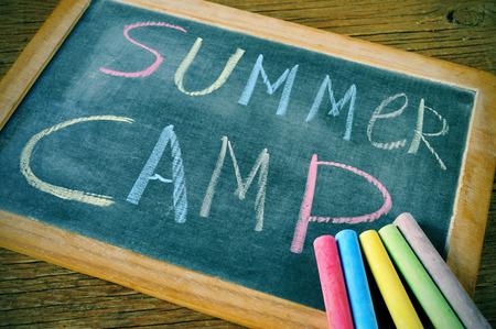 ni�os estudiando: campamento de verano texto escrito con tiza en una pizarra, y algunas tizas de colores diferentes Foto de archivo