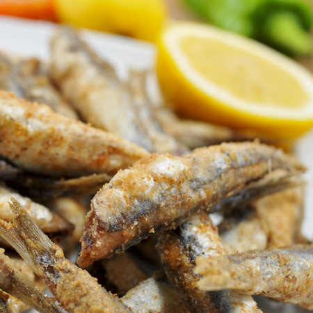 engraulis: closeup of a plate with some spanish boquerones fritos, fried anchovies typical in Spain, served as tapas
