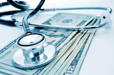 un estetoscopio sobre un montón de billetes de dólares de Estados Unidos, que representa el concepto de la industria de atención médica