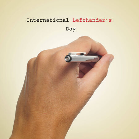 a man left-hand with a pen and the sentence International Lefthanders Day on a beige background photo