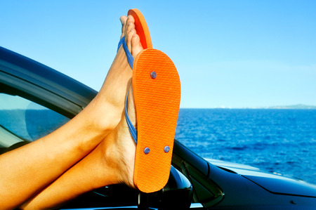 detail of the feet of a young man wearing flip-flops who is relaxing in a car near the ocean