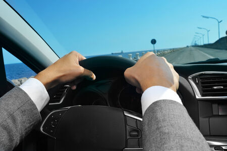 travelling salesman: closeup of a man in suit driving a car
