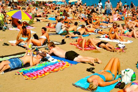 bathers: BARCELLONA, SPAGNA - 19 agosto: Una folla di bagnanti a La Barceloneta Beach il 16 agosto 2013 a Barcellona, ??Spagna. Questa famosa spiaggia ospita circa 500.000 visitatori provenienti da tutto il mondo durante la stagione estiva