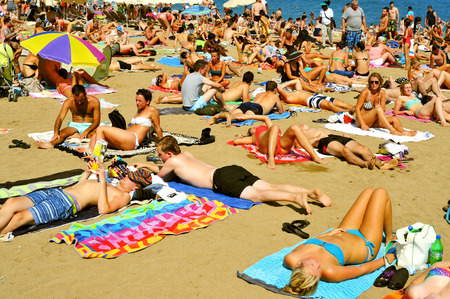 bathers: BARCELONA, SPAIN - AUGUST 19: A crowd of bathers in La Barceloneta Beach on August 16 2013 in Barcelona, Spain. This popular beach hosts about 500,000 visitors from everywhere during the summer season