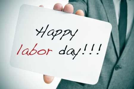 a man wearing a suit showing a signboard with the text happy labor day written in it