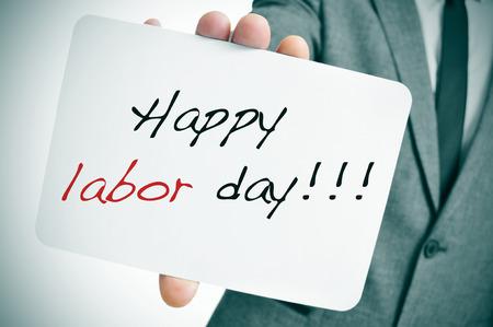 the working day: un hombre que llevaba un traje que muestra un letrero con el texto del día de trabajo feliz escrito en él