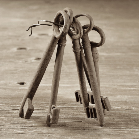immovable: some old and rusty keys on a rustic wooden table, in sepia tone Stock Photo