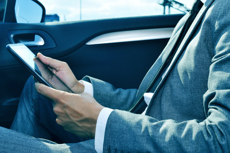 travelling salesman: closeup of a young businessman using a tablet in a car Stock Photo
