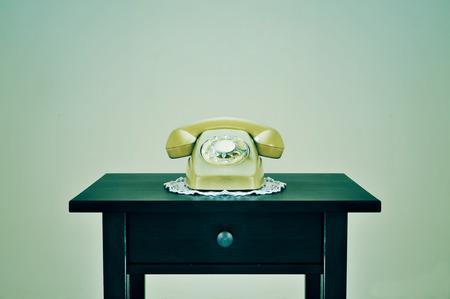 rotary dial telephone: beige viejo tel�fono de disco en una mesa, con un efecto retro Foto de archivo