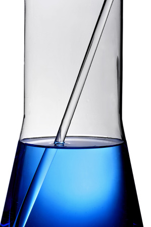 assays: detail of a laboratory flask with a blue liquid and a stirring rod on a white background Stock Photo