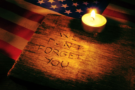 not to forget: the sentence we do not forget you carved on wooden and the flag of the United States and a lighted candle Stock Photo