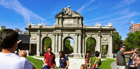 Madrid, Spain - August 13, 2014: Tourists taking pictures of La Puerta de Alcala in Madrid, Spain. This historical gate is one of the most popular landmarks in the city