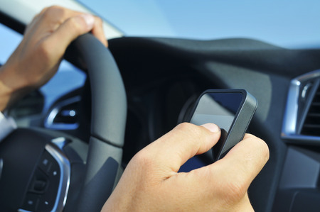 closeup of a man using a smartphone while driving a car