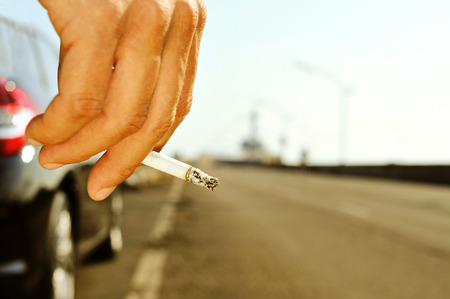 no smoking: closeup of a man with a burning cigarette in his hand while is waiting besides a car parked next to a no traffic road