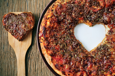 closeup of a barbecue pizza with a heart-shaped cutout on a rustic wooden table photo