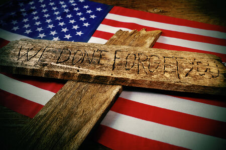the sentence we do not forget you carved on a wooden cross over the flag of the United States photo