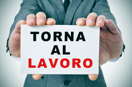 lockout: businessman holding a signboard with the text torna al lavoro, back to work in italian, written in it