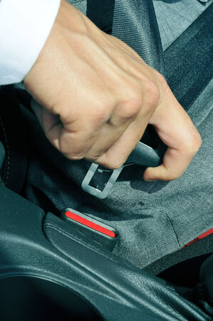 travelling salesman: closeup of a man fastening the car safety belt