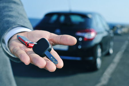man in suit offering a car key to the observer, with a car in the background Stockfoto