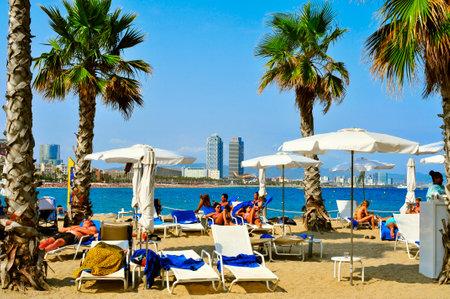bathers: Barcellona, ??Spagna - 19 ago 2014: Bagnanti si trova in lettini a Sant Sebastia Beach a Barcellona, ??Spagna. Sullo sfondo, Torre Mapfre e Hotel Arts, due dei punti di riferimento della citt�