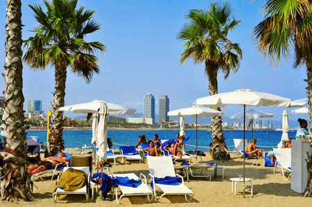 bathers: Barcelona, Spain - August 19, 2014: Bathers lying in loungers in Sant Sebastia Beach in Barcelona, Spain. In the background, Mapfre Tower and Hotel Arts, two of the landmarks in the city Editorial