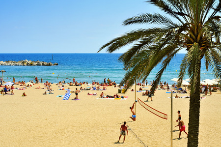 catalonia: Barcelona, Spain - August 19, 2014: Bathers in La Barceloneta Beach in Barcelona, Spain. This popular beach hosts about 500,000 visitors from everywhere during the summer season Editorial