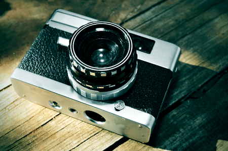 photojournalist: a old camera on a rustic wooden surface Stock Photo