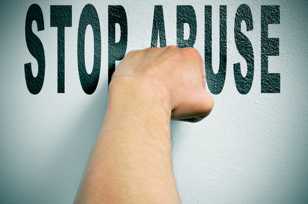 a man punching the text stop abuse, depicting the concept of the fight against all kind of abuse, such as domestic abuse or child abuse photo