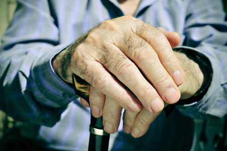 gerontology: closeup of the hands of an old man with a walking stick