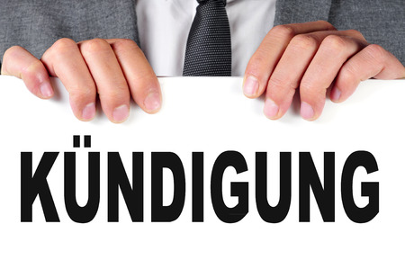 joblessness: a businessman showing a signboard with the word kundigung, dismissal in german, written in it