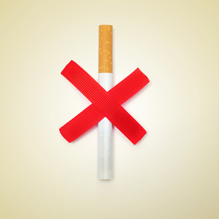 anti tobacco: a cigarette and two crossed red slashes, depicting the concept of no smoking, on a beige background, with a retro effect Stock Photo