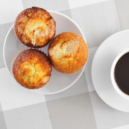 madalena: a plate with some magdalenas, typical spanish plain muffins, and a cup of coffee on a set table Stock Photo