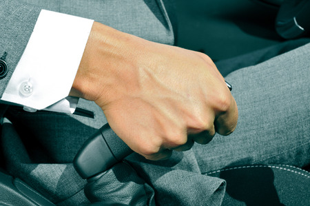 travelling salesman: closeup of a man in suit pulling the hand brake of a car