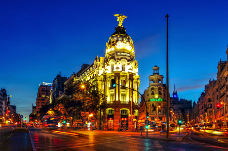 neoclassical: Madrid, Spain - August 12, 2014: The famous Metropolis Building between Gran Via and Calle de Alcala at night in Madrid, Spain. Calle de Alcala is the longest street in the city