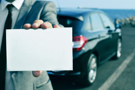 car retailer: closeup of a man in suit holding a blank signboard with a car in the background
