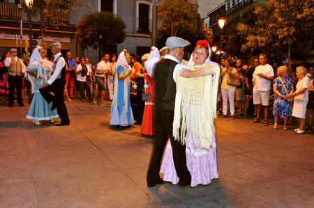 fiestas: Madrid, Spain - August 10, 2014: People dancing the chotis in Madrid, Spain. Chulapos and Manolas (men and women dressed in the traditional way) dance this popular dance of Madrid