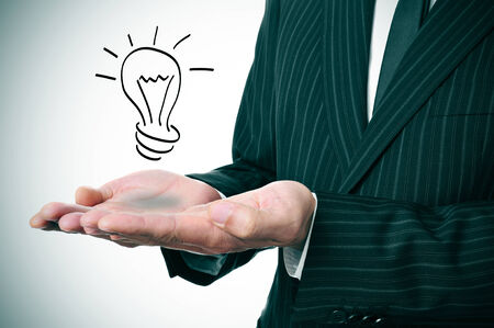 a man wearing a suit with a lightbulb drawn in his hand photo