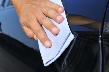 valeting: closeup of the hand of a young man polishing a car
